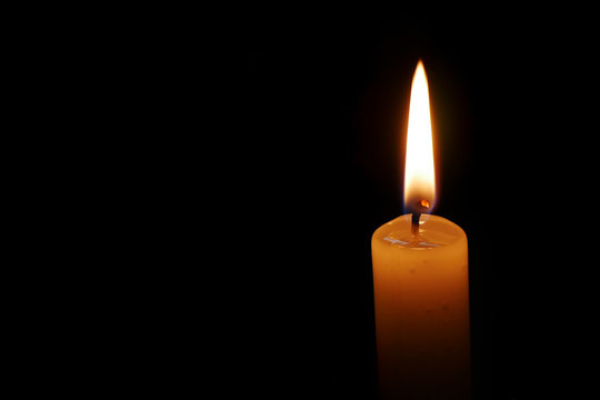 Dramatic burning candle flame on a black background with copy space