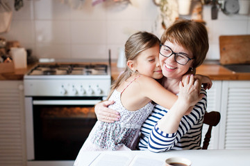 Happy mother is hugging daughter in cozy home kitchen. Woman and cute child girl are smiling. Family is using oven. Kid is enjoying kindness, embrace, care, support. Lifestyle authentic moment. Wall mural