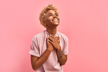 Touched beautiful smiling Afro American girl keeps palms on heart, expresses appreciation, pleasure and gratitude, wears a lavender t-shirt, models over pink background. Confession in love concept