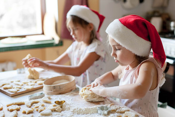 Kids are cooking Christmas gingerbread cookies in cozy home kitchen. Cute children in santa hats play with dough. Little girls make homemade pastries. Lifestyle authentic moment. Children chef concept