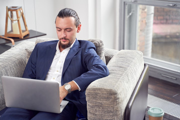 Picture of serious businessman with laptop sitting on sofa in room