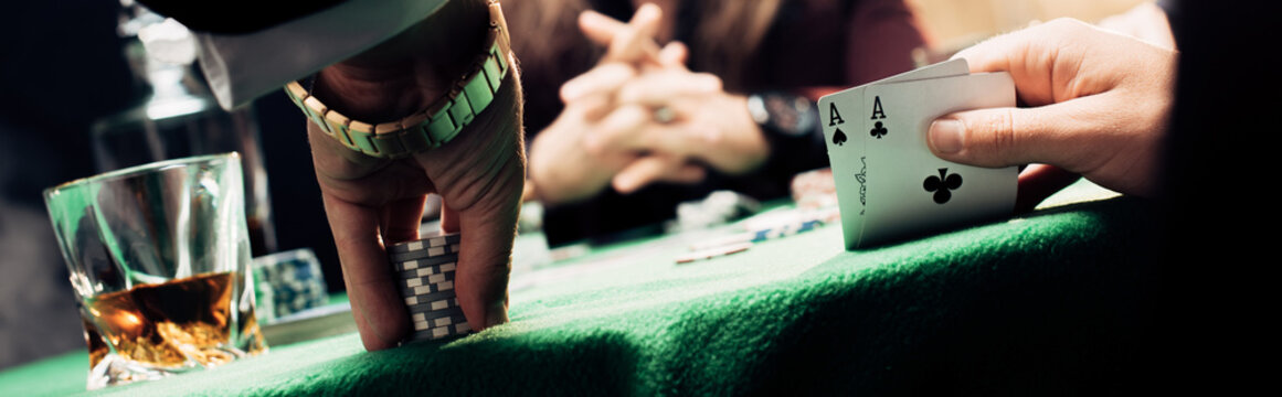 panoramic shot of man touching playing cards and poker chips near player