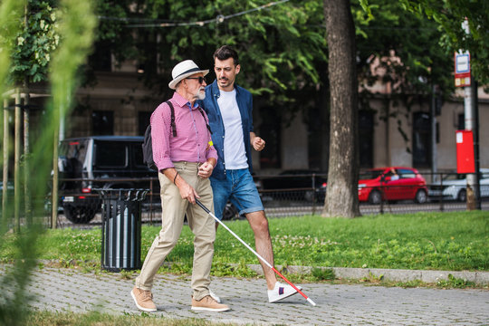 Young man and blind senior with white cane walking on pavement in city.