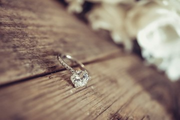 Beautiful toned picture with diamond wedding ring on a wooden surface against the background of a bouquet of flowers