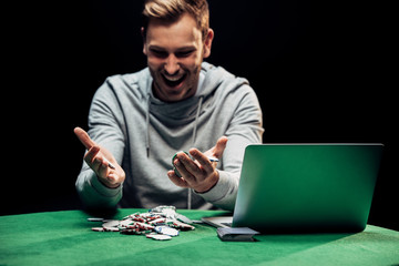 selective focus of happy man looking at poker chips near laptop isolated on black