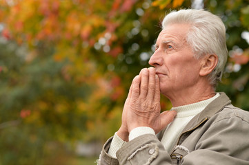Portrait of a thoughtful senior man praying in autumn park