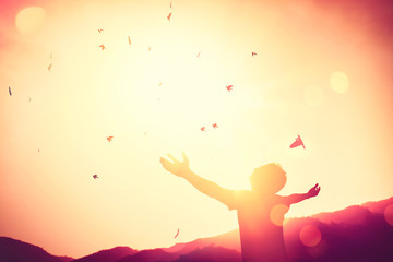 Freedom feel good and travel adventure concept. Copy space of silhouette man rising hands on sunset sky double exposure colorful bokeh and bird fly background.