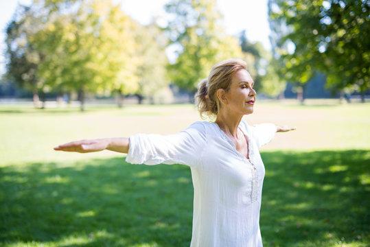 Frau macht Meditationsübungen im Park