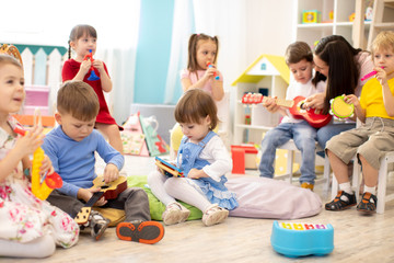 Kindergarten teacher with children on music lesson in day care. Little kids toddlers play together...