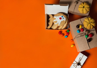 The Concept Of Halloween. Gift boxes, homemade cookies with scary ghosts and bats, colorful candies on an orange background. Free space for your text.