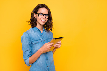 Portrait of cool confident positive freelancer use her tablet work on university project feel content wear stylish clothes isolated over yellow color background