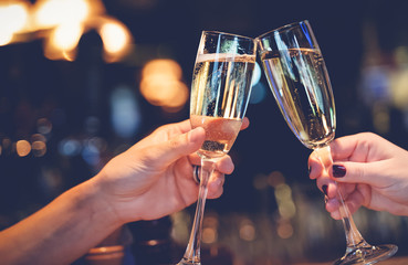 Two glasses with sparkling champagne wine in hands, concept for holiday, wedding valentines Christmas and New Year, bokeh, in a restaurant and cafe