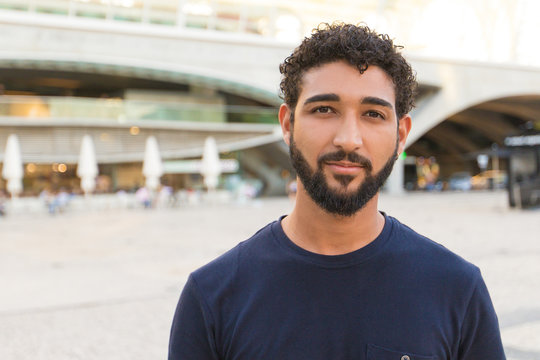 Pensive positive mix raced guy posing in city square. Front portrait on young man with black curly hair and beard wearing blue casual shirt, looking and smiling at camera. Male portrait concept