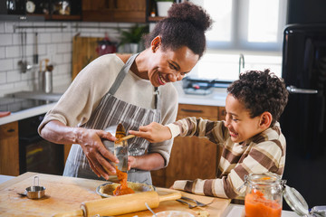 Mother and son baking together. American family. Single mother. Child helping mother.