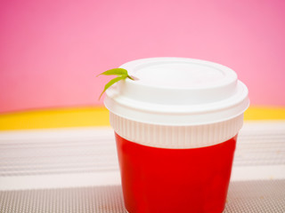 Wall Mural - Red coffee cup and leaf with  pink background.Modern concept