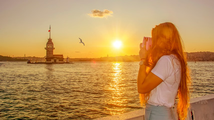 Tourist taking a picture in front of  Maiden Tower (kiz kulesi ) , Istanbul, Turkey. Travel concept