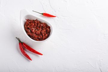 Canvas Prints Hot chili peppers Hot chili pepper paste. Red sauce on white background. Adjika or ajika in Georgian cuisine or harissa in Arabic cuisine. Top view.