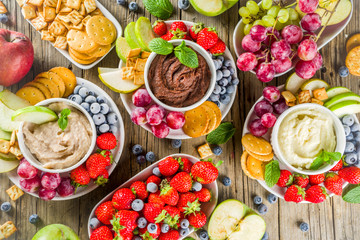 Deurstickers Picknick Vegan food for breakfast, snack. Homemade Sweet Hummus with strawberries, apple, crackers, grapes. Variations of different hummus dessert dips - vanilla, chocolate, caramel.