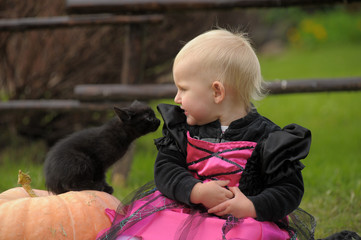 Little girl in a witch costume and a black kitten