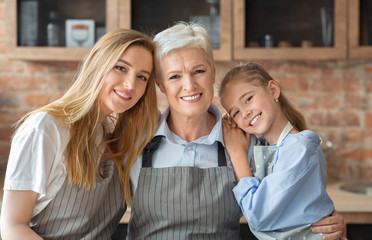 Portrait of mother, daughter and grandmother embracing at kitchen