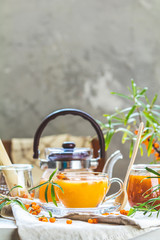 Hot spicy tea with sea buckthorn in glass cup and teapot, selective focus, rustic light background