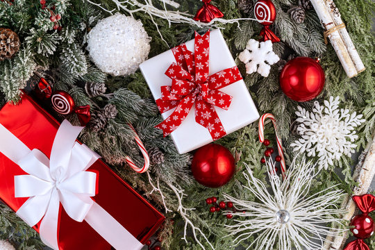 Christmas natural foliage composition with red and white gifts with ribbon, globes, snow flakes, candy cane, berries, sweets, birch sticks and snowy pine or fir branches with cones. Flat lay, top view
