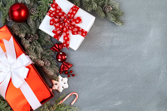 Christmas red and white gifts with ribbon. Red globe, snow flake, candy cane, red berries and sweet with snowy fir branches with cones and foliage over stone like background with copy space. Top view
