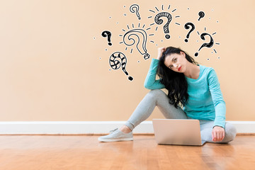 Question marks with young woman using a laptop computer