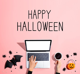 Happy Halloween message with laptop and Halloween decorations - flat lay