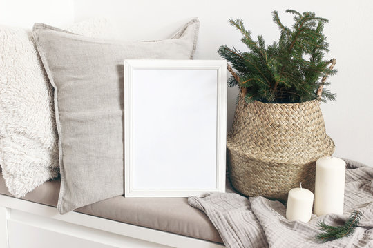 White blank wooden frame mockup with Christmas tree, candles, linen cushions and plaid on the white bench. Poster product design. Scandinavian home decor, nordic design. Winter festive concept.