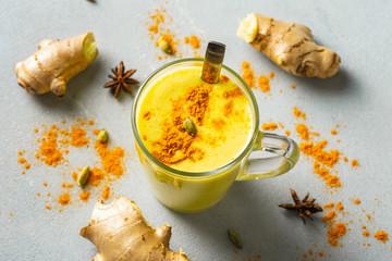 Fototapeta Golden latte on light background. Indian drink turmeric golden milk in glass obraz