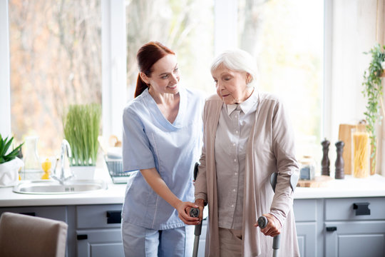 Smiling caregiver helping aged woman to make steps
