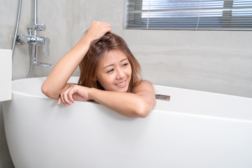 Portrait of young attractive asian girl takes a bath with candles relax in the bathroom. Beauty woman in spa treatments. Healthy perfect glow skin care concept