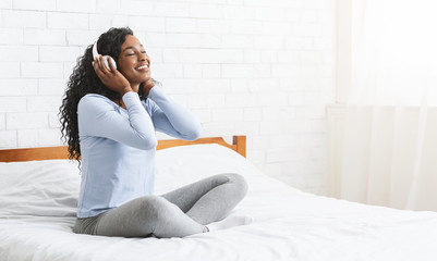 Cheerful young girl listening to music in bedroom