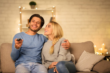 Young couple watching TV on sofa in the evening