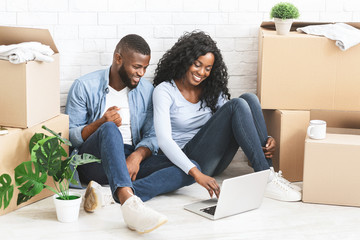 Cheerful couple sitting on floor at new apartment, using laptop