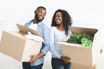Young couple holding cardboard boxes, smiling to each other