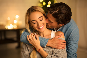 Tender moment. Man kissing wife in front of Christmas tree