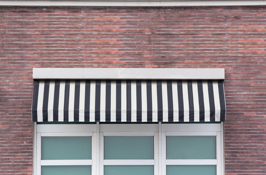 black and white striped awning over white window frame of shop.