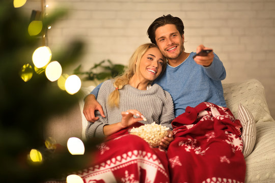 Loving couple watching tv at Christmas eve