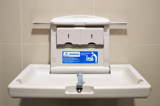 Baby changing station in a public restroom. white plastic diaper table on brown tile wall in toilet.