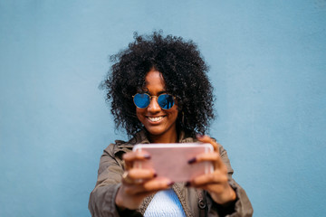 Woman using smartphone, blue background