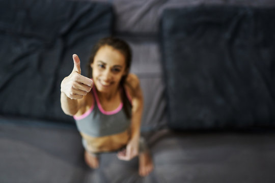 portrait of smiling young woman with muscular naked torso showing thumbs up at inside climbing gym. Top view of hands.