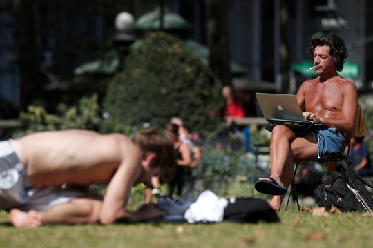 A man works on a computer in the sun at Bryant Park in New York City