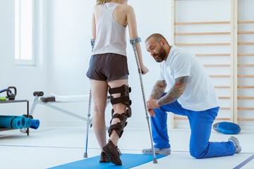 The girl after a stroke with an orthosis on a crutch leg is exercising on a blue mat in a gym in a hospital