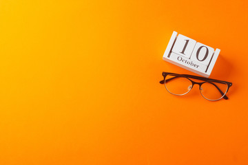 Glasses and wooden calendar, world view day, concept, on orange background, top view