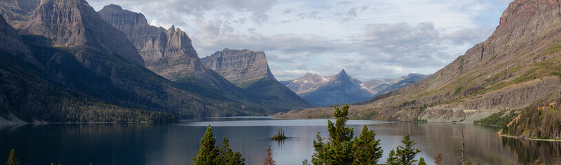 Beautiful Panoramic View of a Glacier Lake with American Rocky Mountain Landscape in the background during a Cloudy Summer Morning. Taken in Glacier National Park, Montana, United States. Fotobehang