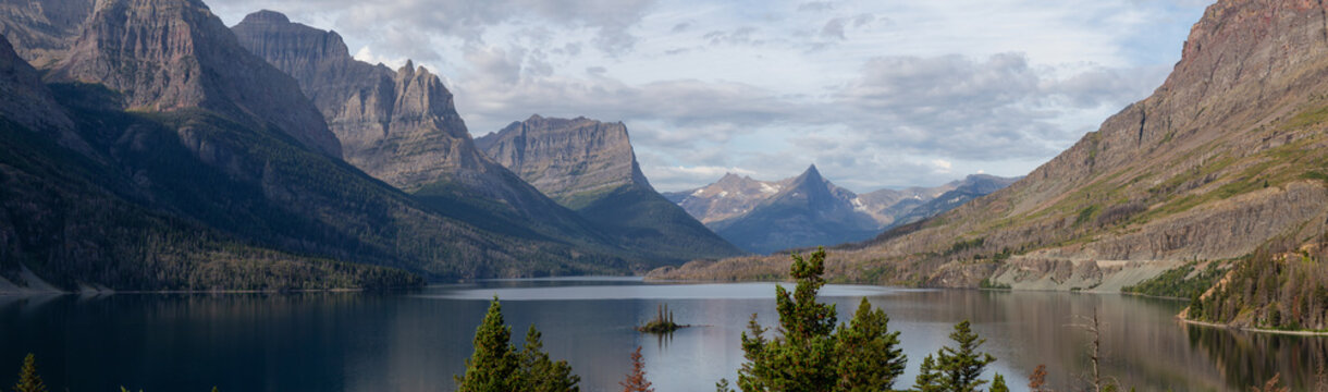Beautiful Panoramic View of a Glacier Lake with American Rocky Mountain Landscape in the background during a Cloudy Summer Morning. Taken in Glacier National Park, Montana, United States.