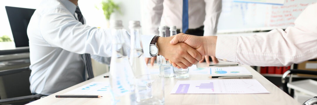 Two adult caucasian business people shake hand against office background. Pre-trial dispute resolution and contract support concept