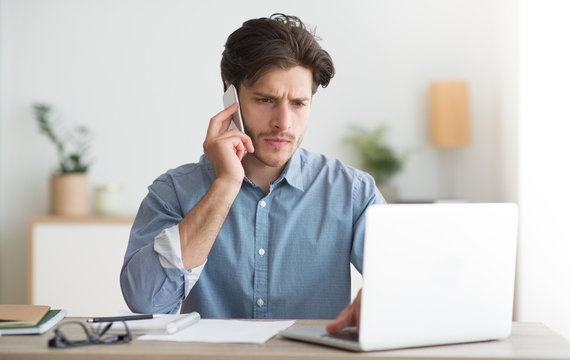 Businessman Talking On Mobile Phone Sitting At Workplace